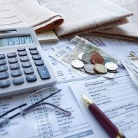 Unterlagen mit Rechner, Stift, Brille und Geld