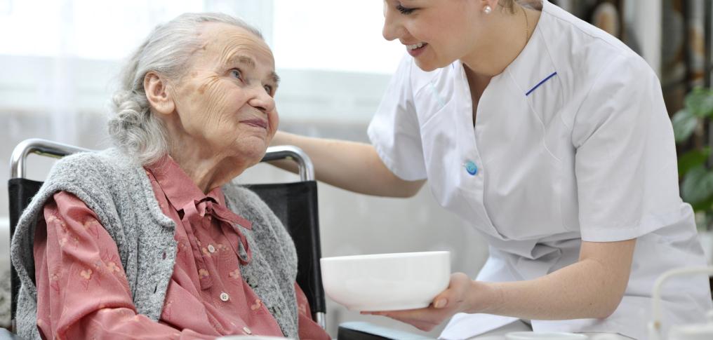 alte Dame wird von Pflegerin versorgt