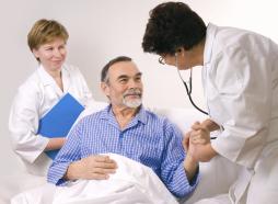 Ärzte bei Untersuchung am Krankenbett eines Patienten