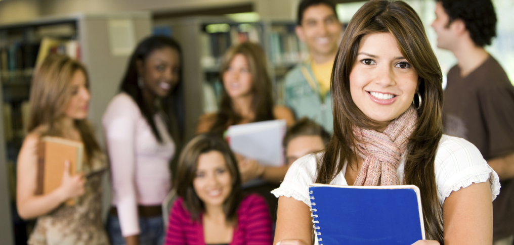 lächenlde Studentin mit Unterlagen zwischen beiden Händen im Hintergrund Mitstudenten