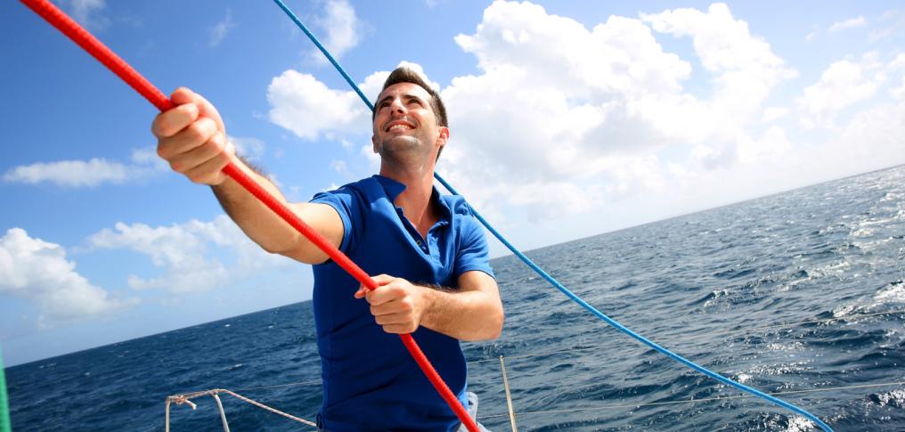 Mann setzt Segel auf einem Boot