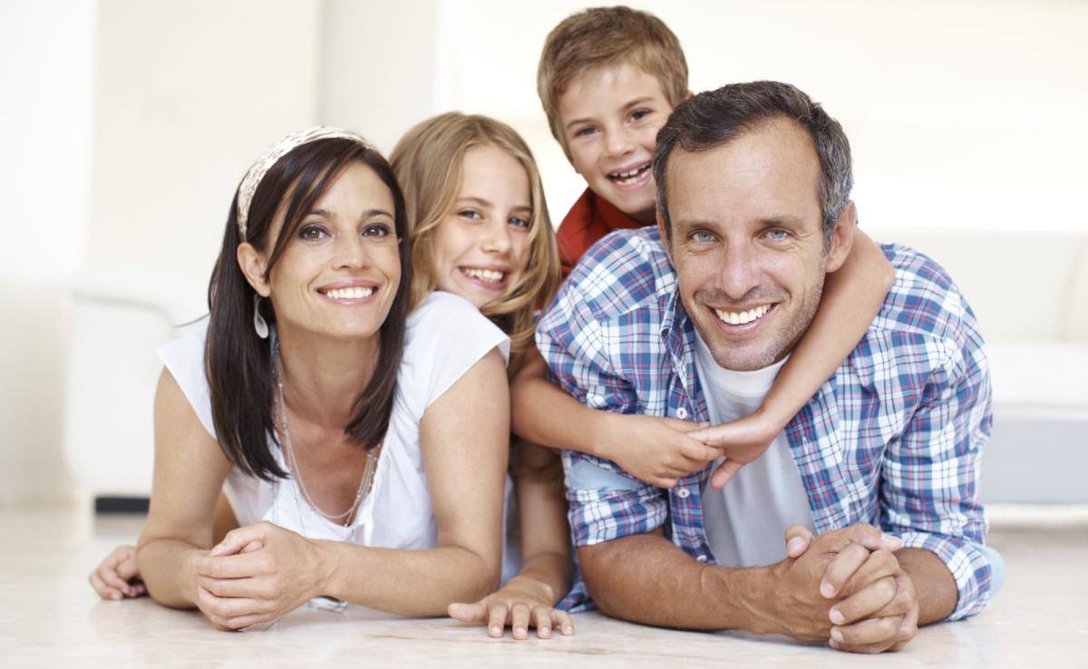 glückliche Familie mit Kinder liegend auf dem Boden