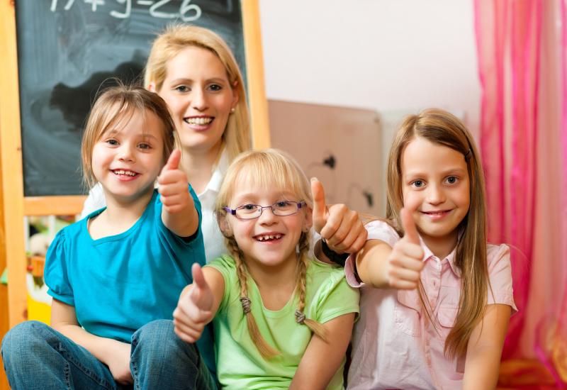 Lehrerin mit Grundschüler und Daumen nach oben