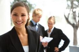 lächelde Frau im Vordergrund mit unterhaltende Personen im Hintergrund
