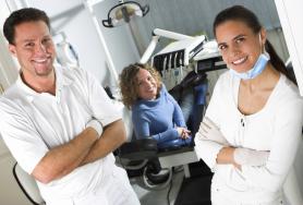 lächelnde Zahnärzte mit Patient im Hintergrund